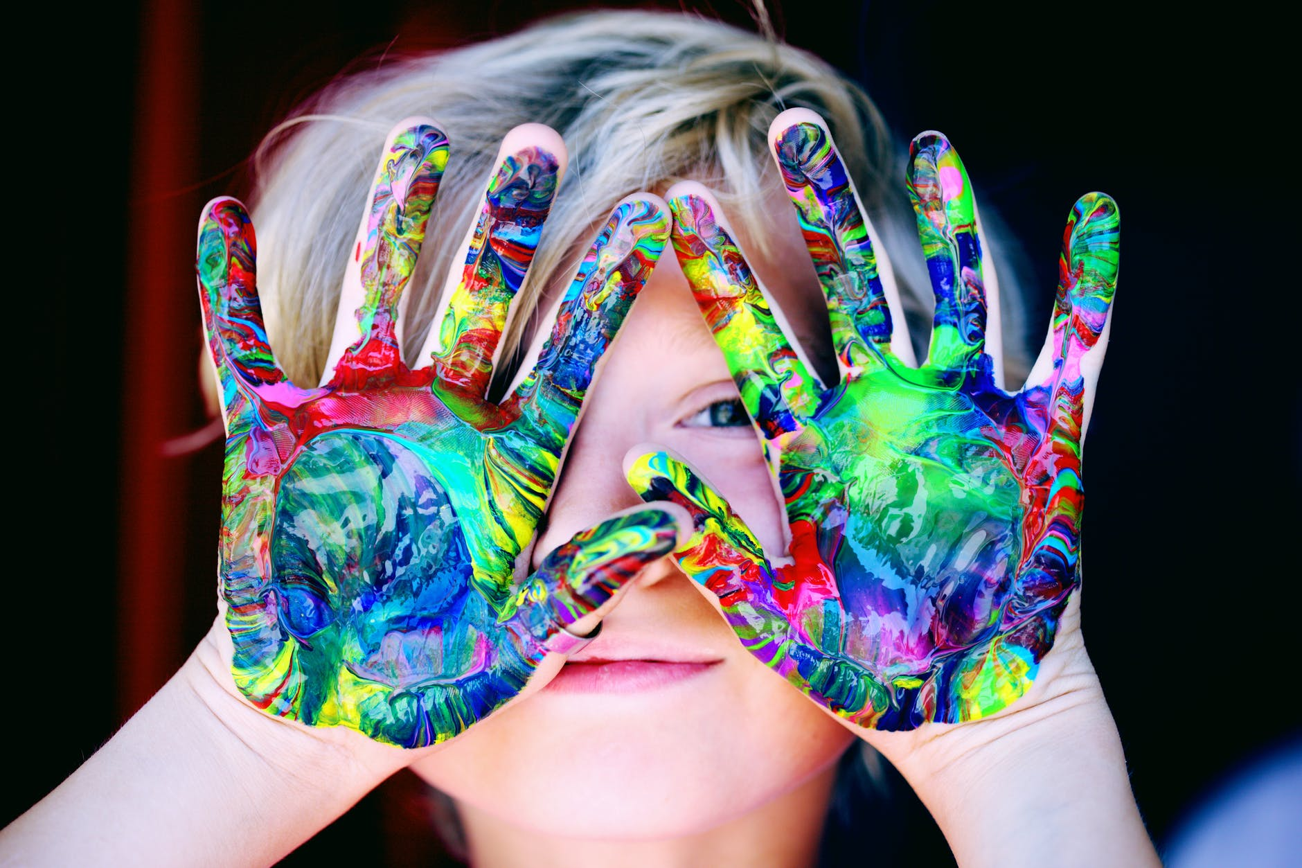 Child holding his hands up.  Hands are covered in multiple paint colors including red, green, blue, purples, yellow.
