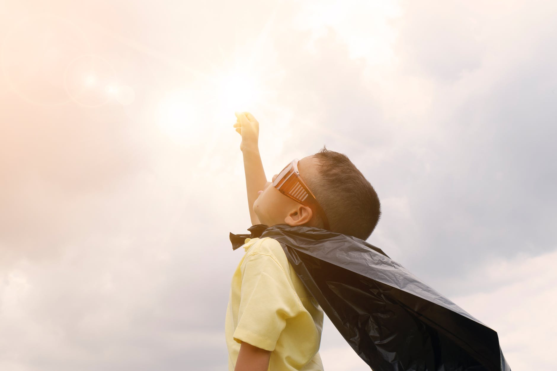 Young child about five looks up to sky with raised hand.  Child is dressed in a cape made out of a garbage bag and red sunglasses on.