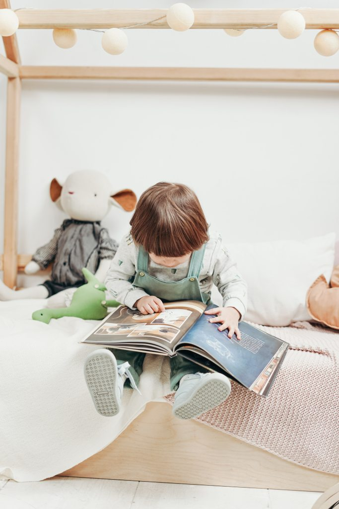 Child in long sleeves and trousers reading a book