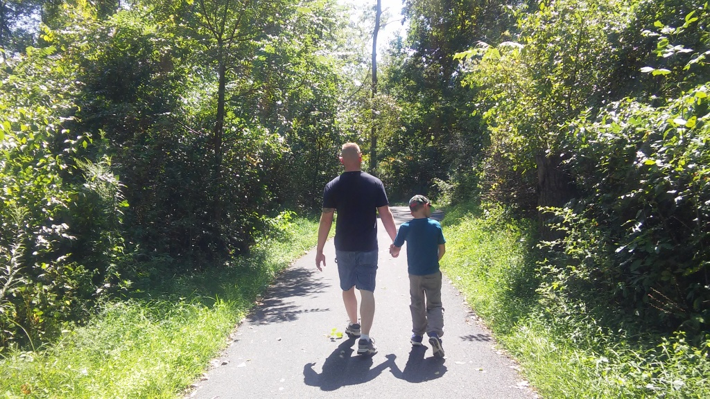 Daddy son time - investing in the future. The men walk on a pathway through the woods in Gettysburg, PA.
