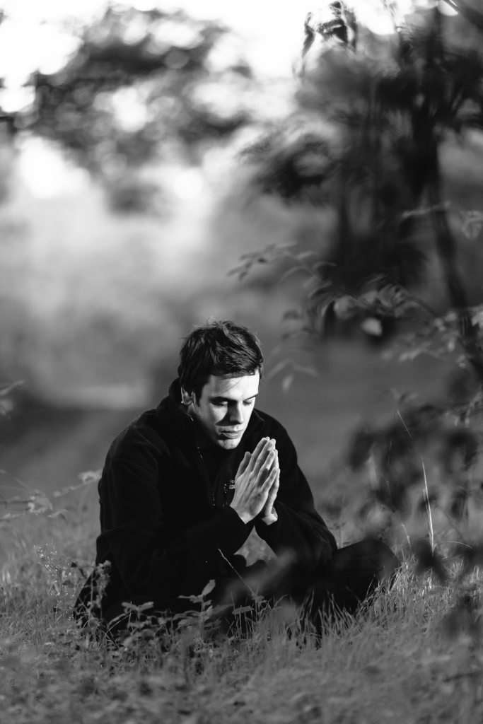 grayscale-photography-of-man-sitting-on-grass-field