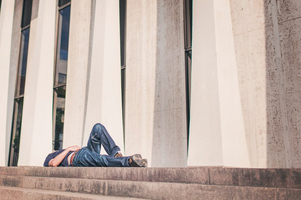 Man laying down on steps of building during daylight hours