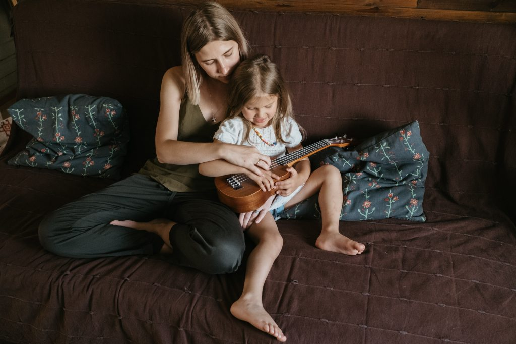 woman-in-grey-sleeveless-top-with-girl-on-her-lap-playing