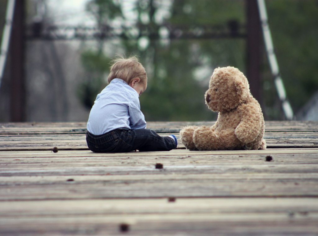 Friendship is forever.  Child with stuffed Teddy on a wooden bridge.